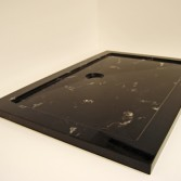 Black marble shower tray with white veining.