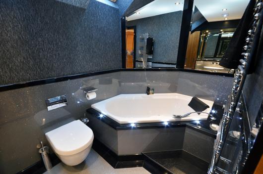 Luxury bathroom design. Silver high gloss sparkle panels surrounding white diamond bath