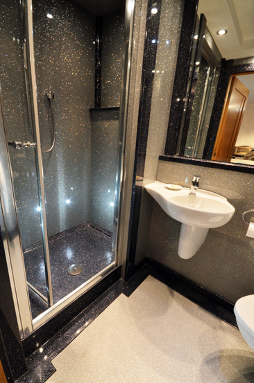 Glamorous luxury bathroom with beautiful silver sparkle panels and black sparkly shower tray