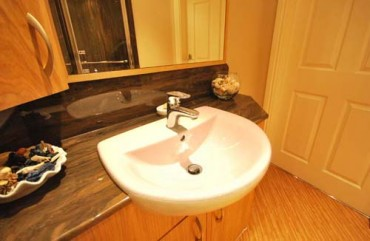 Brown marble vanity top with white sink and mixer tap.