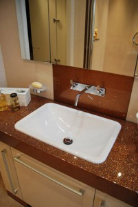 Brown sparkly counter top with white sink and cream splash panels.