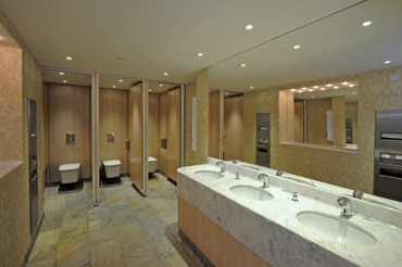 Public bathroom with marble look vanity top with multiple undermounted wash basins.