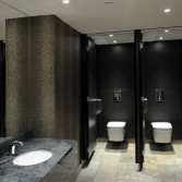 Public washroom with grey tiled floor and marble grey vanity tops with wsahbasin