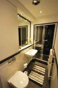 Narrow bathroom with black and white panels and dado.