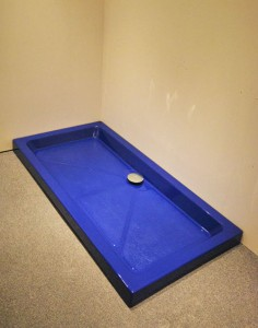 Bright blue shower tray with silver waste finish.