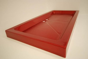 Bright red shower tray with 2 waste outlets with sparkle.