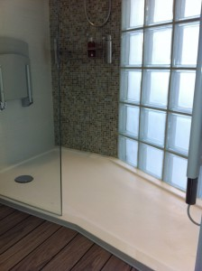 White shower tray in shower area with glass blocks and mosaic wall.