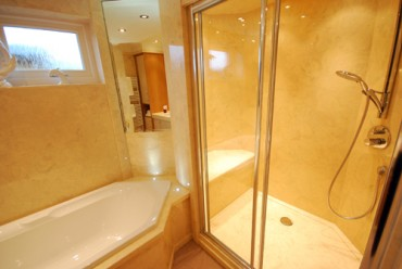 Large cream bathroom shower with seat and diamond shaped bath.