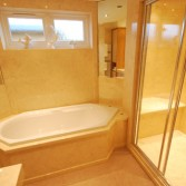White diamond shaped bath with large walk in shower with cream marble finish.
