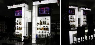 Back lit bar in white with black shelves.