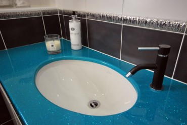Bright blue sink surround with black tiled splashback.