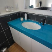 Black and white bathroom with bright blue vanity top.