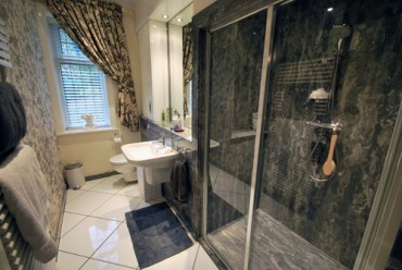 Granite bathroom with large shower and washroom area