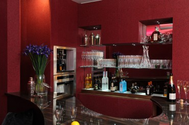 Bar area with red wallpaper, brown marble shaped bar top.