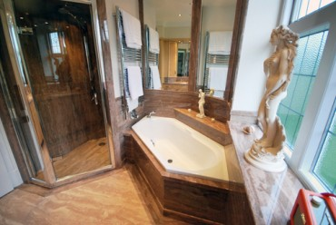 Luxury bathroom with large walk in shower, diamond shape bath and mirrors in granite.