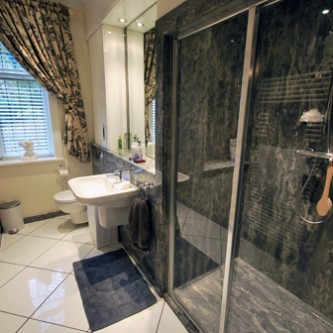 Shower and surfaces in 'Gritstone' marbled granite finish.