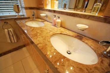 Cream and brown marble vanity top from Versital with two undermounted ceramic basins.