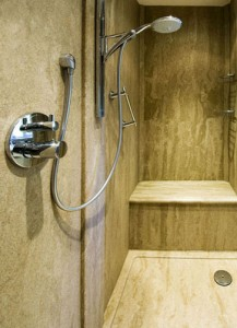 Bespoke shower tray, shower seat and panels in brown granite finish.