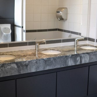 Washroom vanity top in 'Gritstone' marbled granite finish.