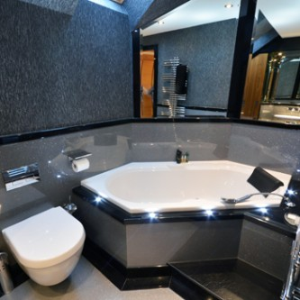 Stunning bathroom design with diamond shaped bath and surrounded by Versital silver panels.  Designer wallpaper finishes the room perfectly