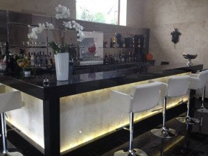 Home bar installation using marble back lit bar panels in onyx.