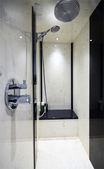 Large walk in marble shower with built in seat