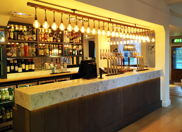 Modern bar design with feature light bulbs and marble bar top