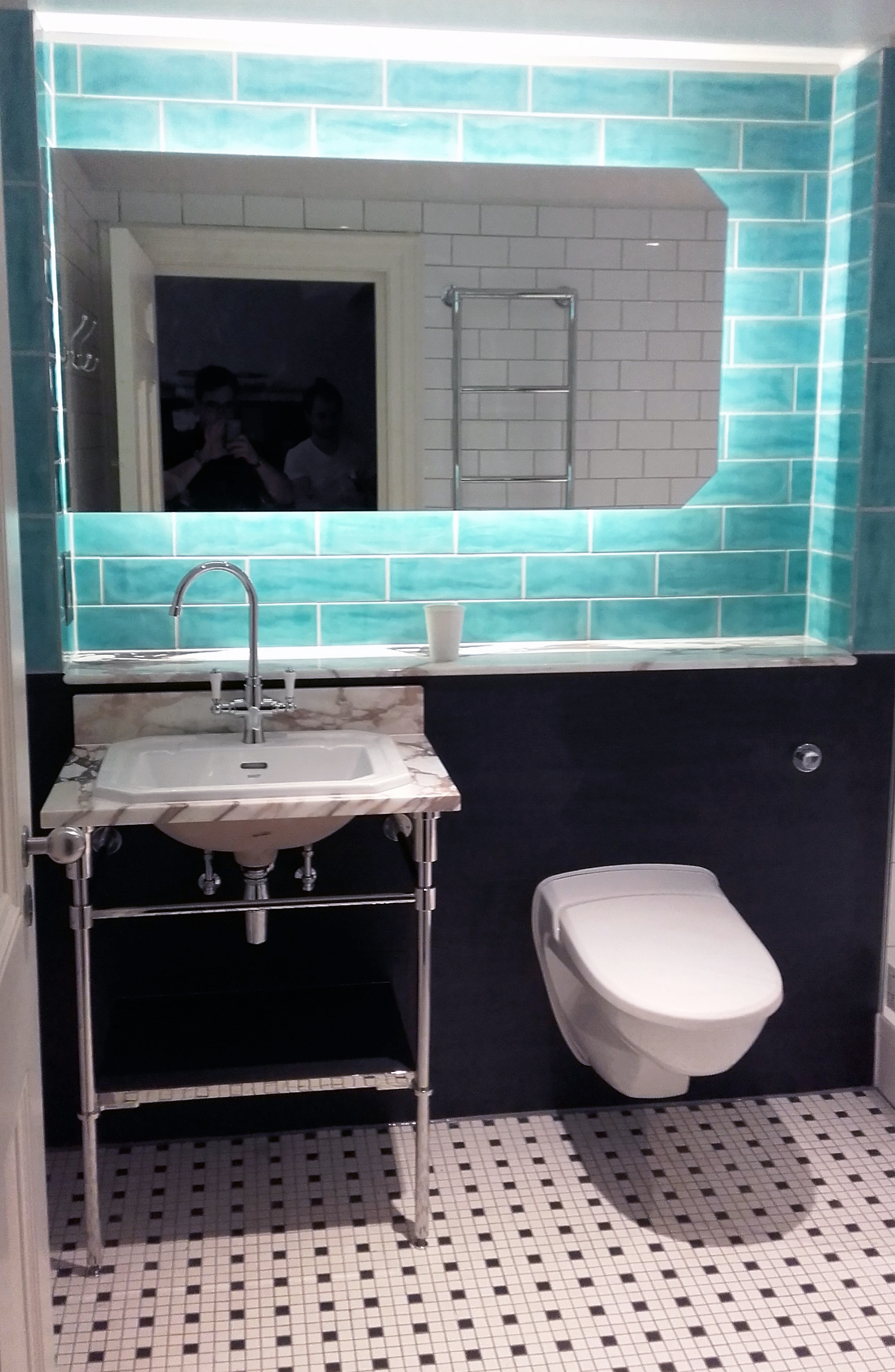 Modern bathroom with white marble vanity and turquoise blue tiles ...