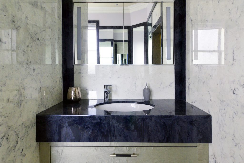 Dark grey marble vanity top from versital with an undermounted sink and a sycamore under sink cabinet