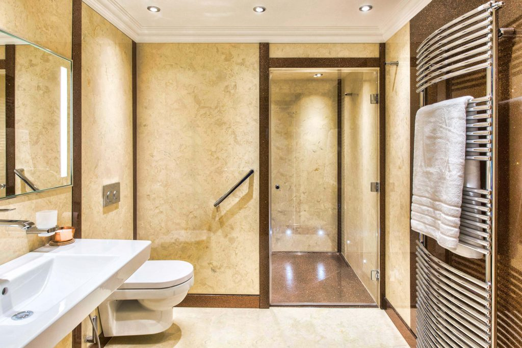 Large master bathroom in cream marble with contrasting sparkle skirting