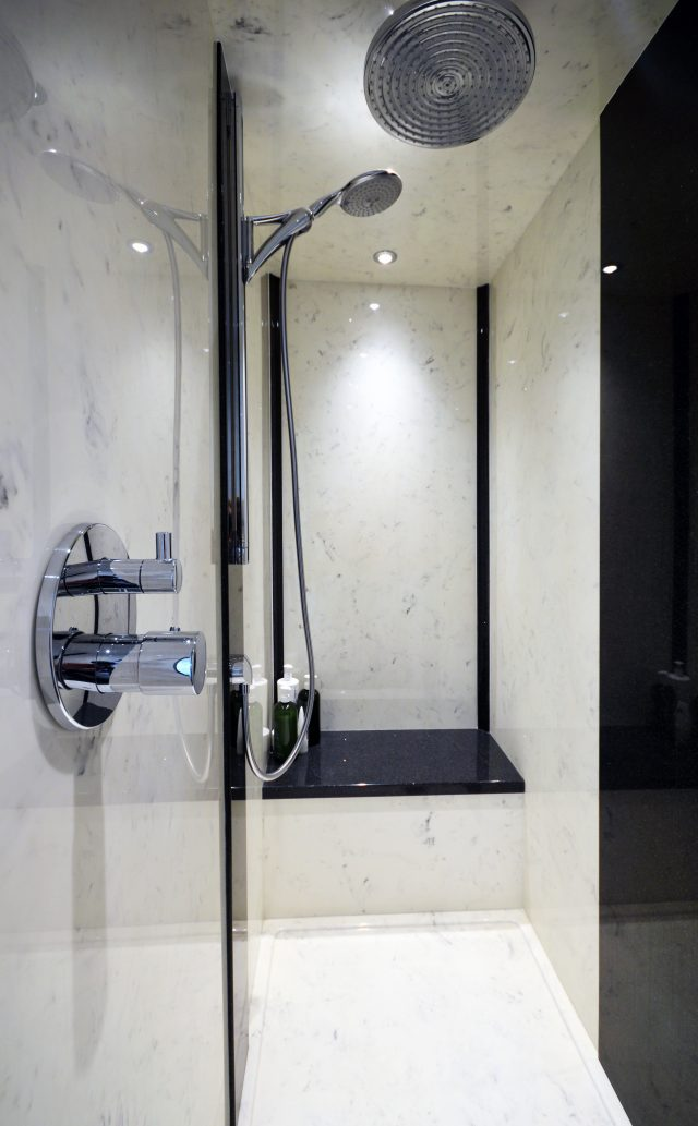 White marble shower enclosure with complimentary wall panels and shower tray