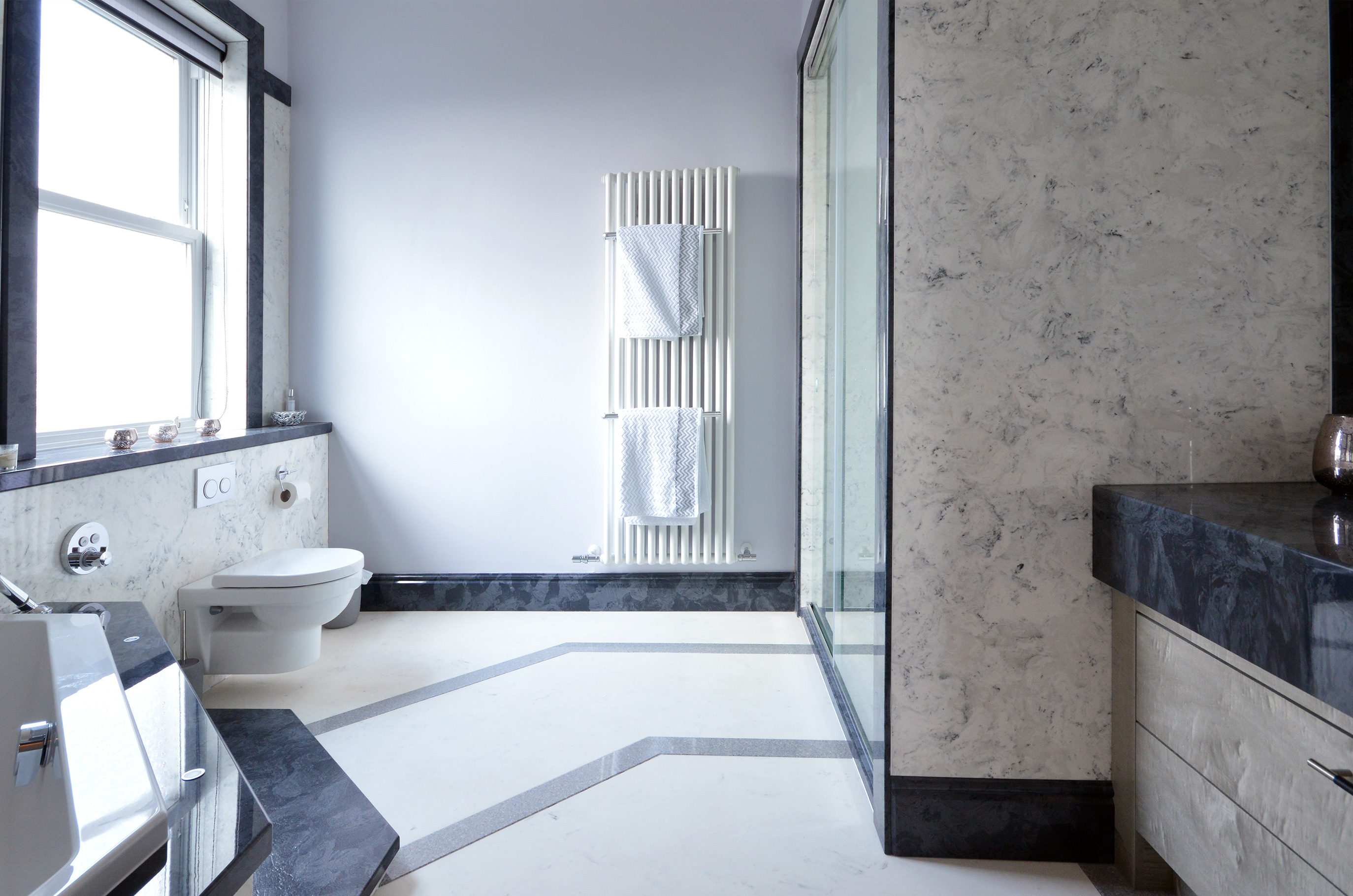 Marble bathroom wall panels in arabesque contrasted by Gloucester marble skirting and architrave
