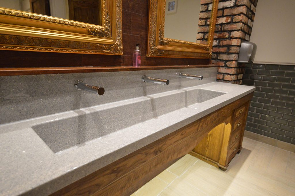 Washroom vanity in granite with an integrated basin and a wooden base