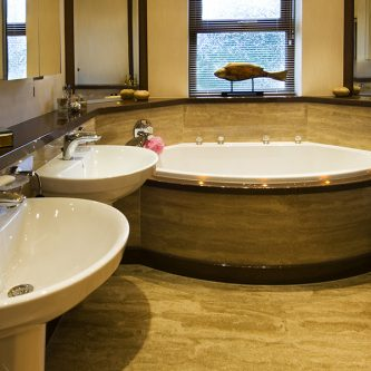 Floor Slabs and Bath Front Panel in Sandstone Granite Finish and Decorative Vanity Top in Coco-Loco Reflect Finish