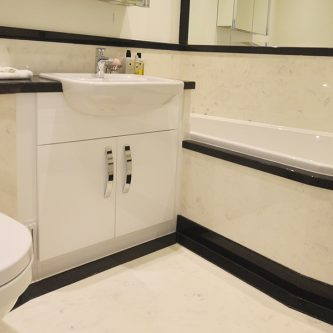 Wall Panels and Bath Front Panel in Sicilian Marble Finish and Vanity Top, Bath Deck and Skirting in Noire Granite Finish