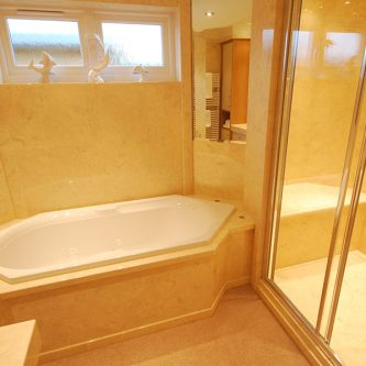 Wall and Shower Panels, Bath Front And Floor Slab in Bone Marble Finish and Shower Tray in Perlato Marble Finish