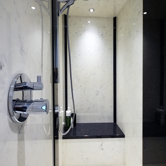 Wet Room in Arabesque Marble Finish with Decorative Panels in Noire Reflect Sparkle Finish