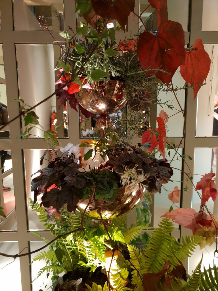 hanging greenery baskets with metal accents at sleep and eat
