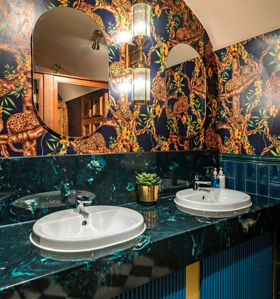 Dark green marble vanity top and jungle theme wallpaper